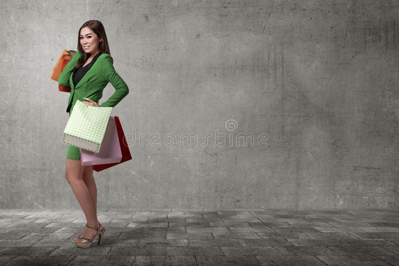 Happy asian business woman opening her shopping bag royalty free stock images