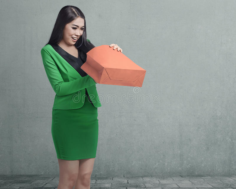 Happy asian business woman opening her shopping bag stock photos