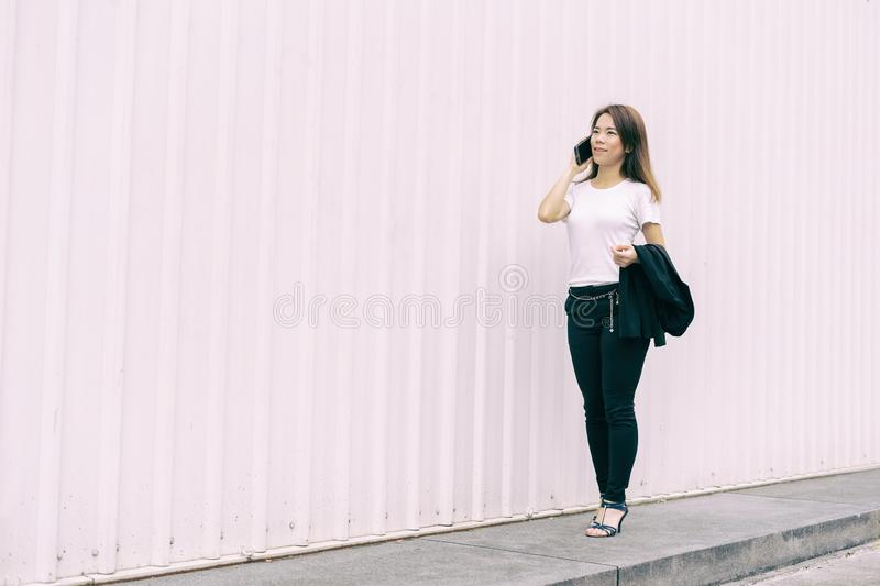 Happy Asian business woman walking and talking smart phone on street in city with white color wall background stock image