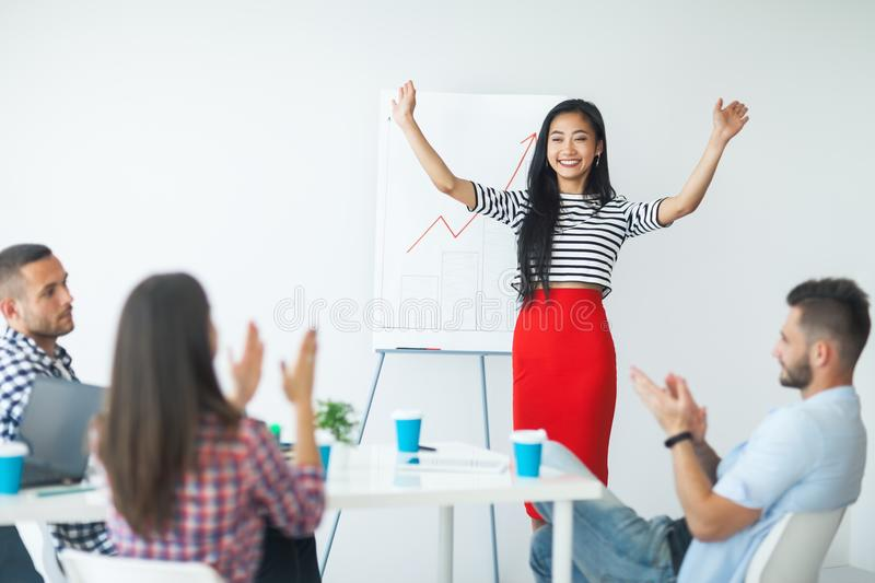 Happy asian business woman celebrating success after presentation stock photo