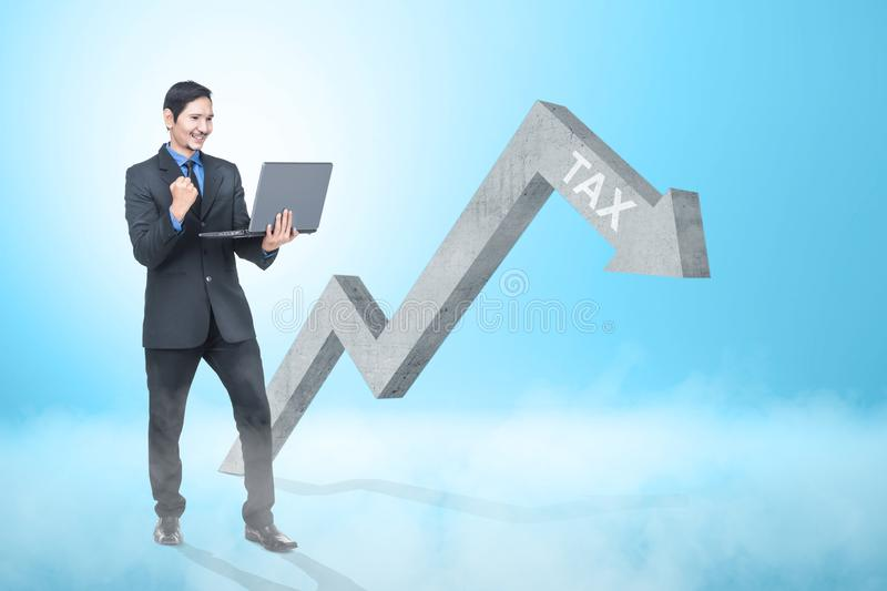 Happy asian businessman with laptop looking at declining tax graph arrow. Taxes concept stock images