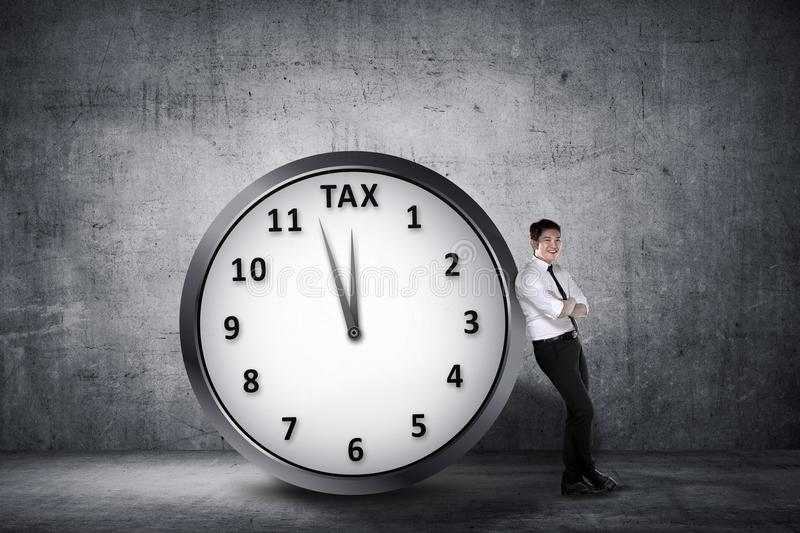 Happy asian businessman lean back on the clock with deadline tim royalty free stock image