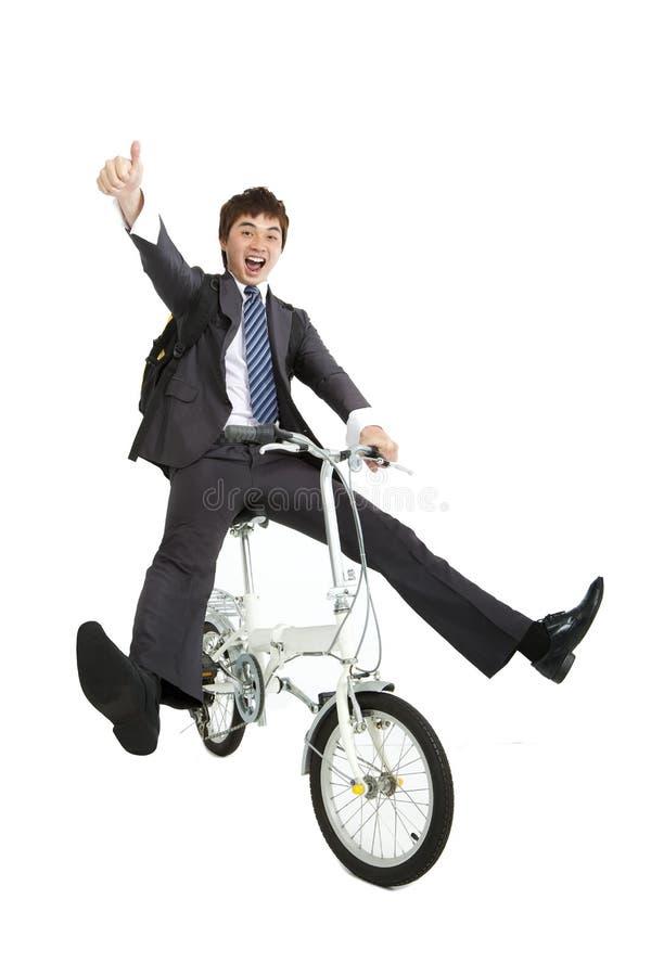 Happy asian businessman riding bike stock photography