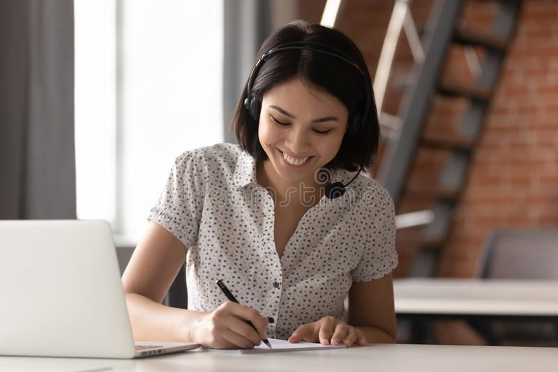 Happy asian businesswoman wearing headset make notes on conference call. Happy asian businesswoman wearing headset make notes talk by conference call doing video stock photography