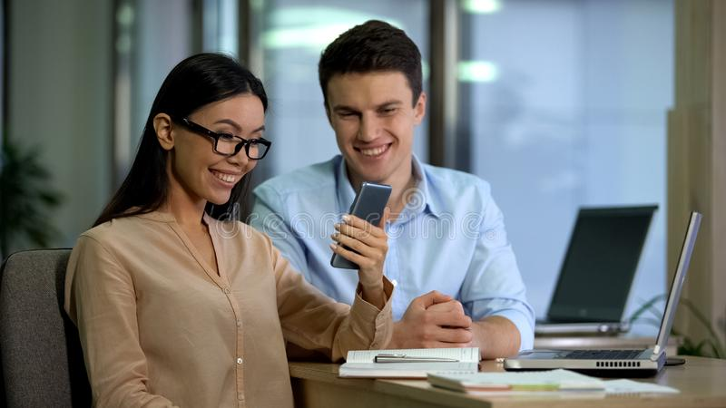 Happy asian caucasian colleagues reading mail on gadget, receiving good news stock photo