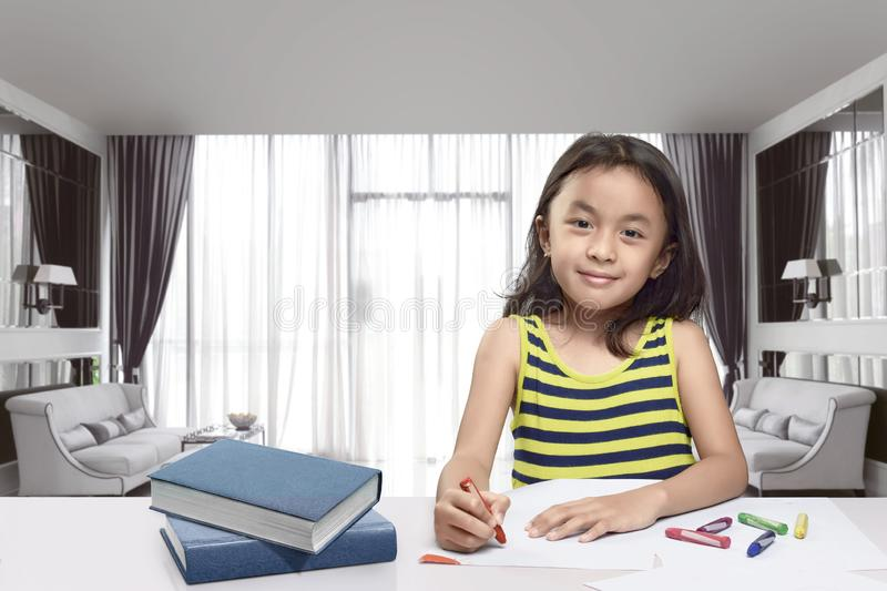 Happy asian child with colorful crayon drawing on white paper stock photos