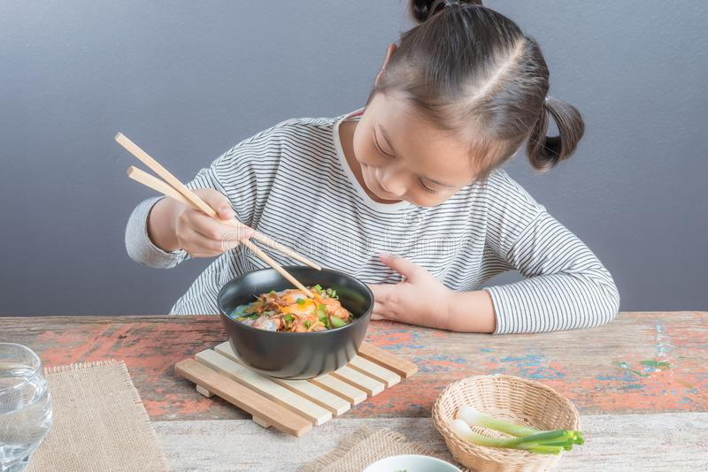 Happy Asian child eating delicious noodle. Happy Asian child age 6 years eating Stir fried yellow noodle `mee hokkian phuket`, small thai girl eating noodles royalty free stock images