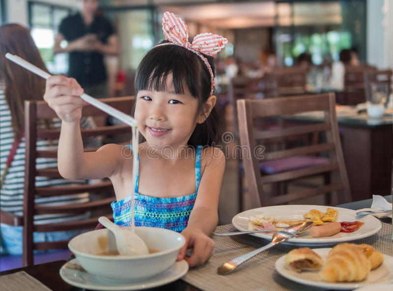 Happy Asian child eating delicious noodle with chopstick. In the restaurant royalty free stock image
