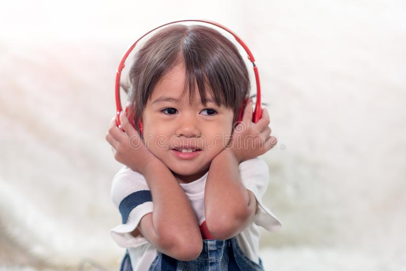 Happy Asian child enjoy listening to music with headphones royalty free stock photography