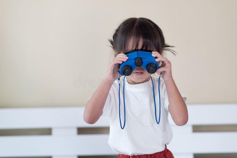Happy Asian child enjoy looking through binoculars, Travel and adventure kid concept stock photo