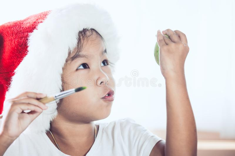 Happy asian child girl drawing and painting on easter egg stock images