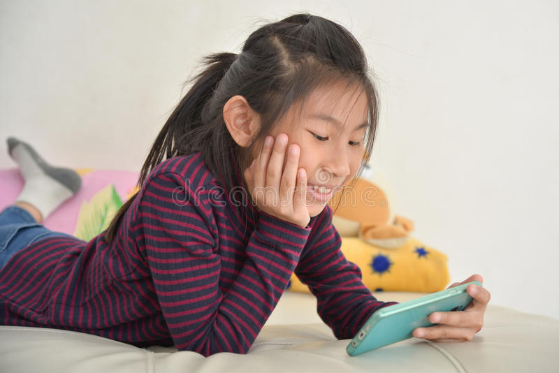 Happy Asian child girl looking at smart phone stock image