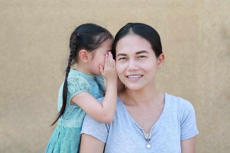 Happy Asian child girl sharing a secret to her mom. Kid girl whispering gossip a something to mother ear royalty free stock image