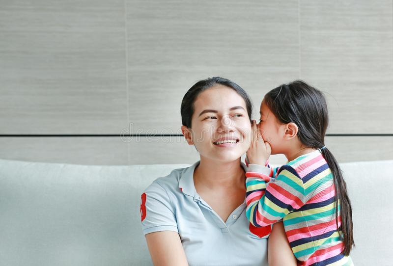 Happy Asian child girl sharing a secret to her mom in the living room at home. Kid girl whispering gossip a something to mother stock image