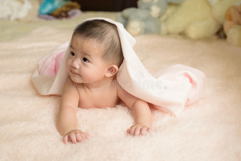 Happy asian child lay on bed. stock photography
