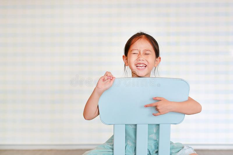 Happy Asian child preschool girl in a Kindergarten room poses on plastic baby chair.  stock photography
