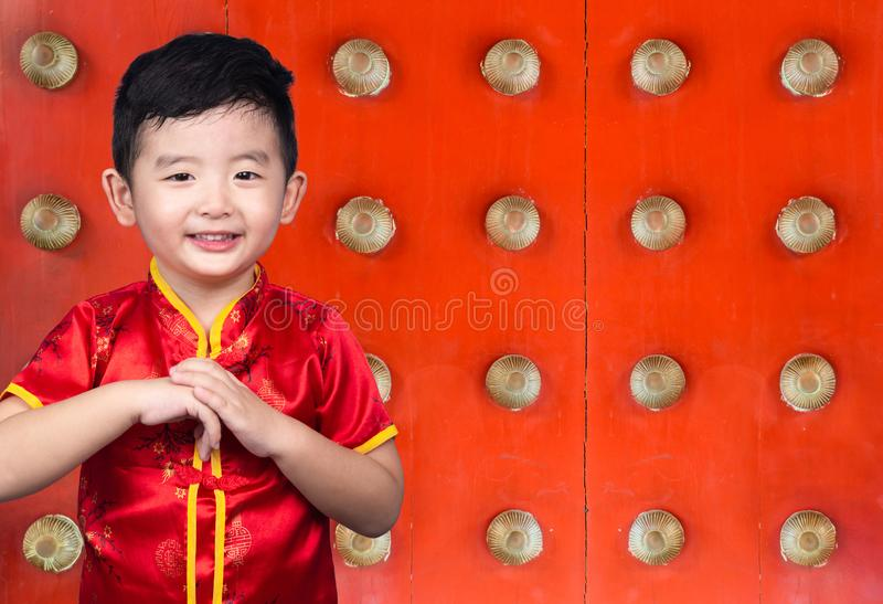 Happy Asian Chinese kid wearing red traditional suit on Chinese temple or joss house background celebration for Chinese New Year royalty free stock photography