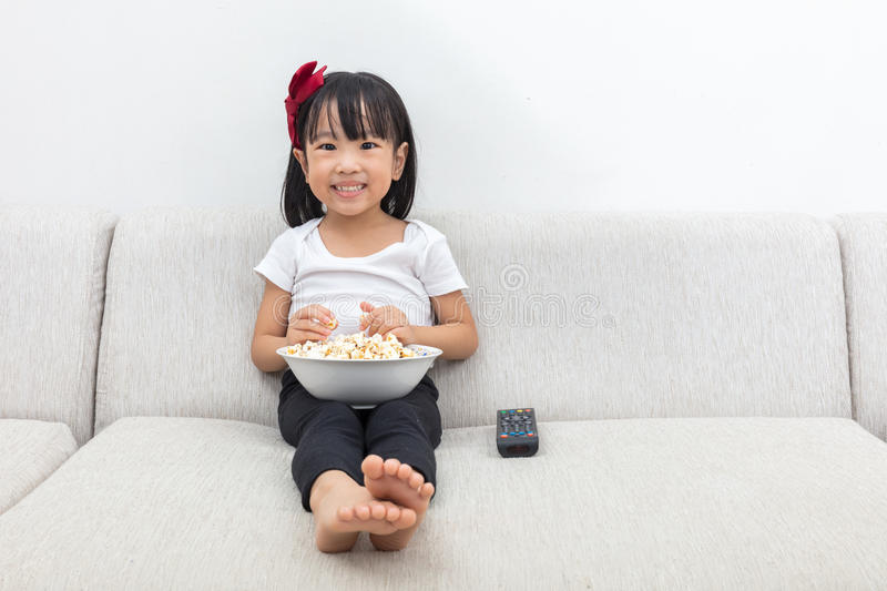 Download Happy Asian Chinese Little Girl Eating Popcorn On The Sofa Stock Photo - Image: 83703107