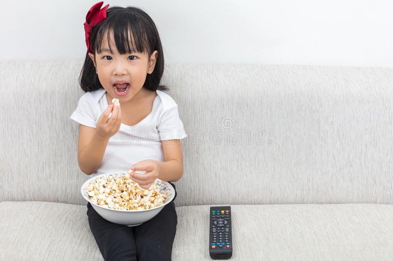 Download Happy Asian Chinese Little Girl Eating Popcorn On The Sofa Stock Photo - Image: 83703307