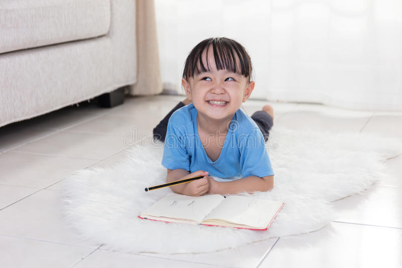 Happy Asian Chinese little girl lying on the floor drawing royalty free stock photography