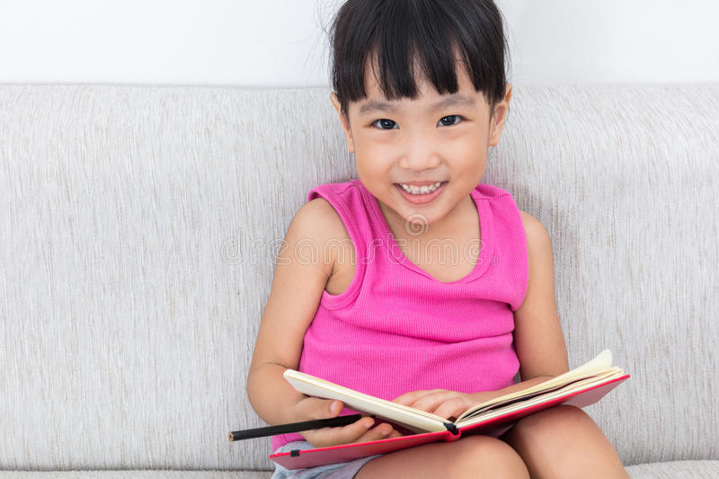 Happy Asian Chinese little girl sitting on sofa writting book royalty free stock image