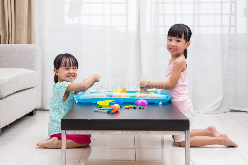 Happy Asian Chinese little girls playing kinetic sand at home royalty free stock photos