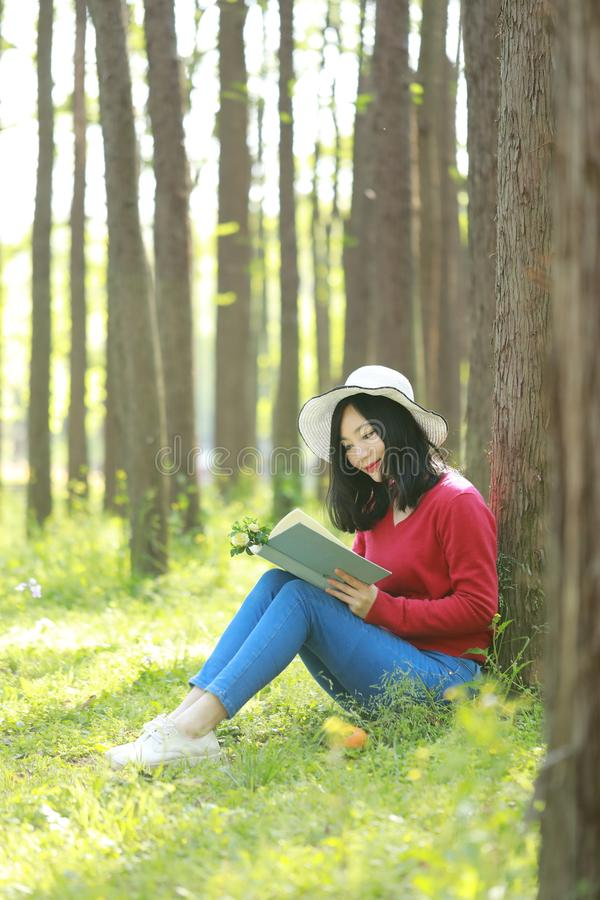 Happy Asian Chinese woman beauty girl smile and read a book in forest spring park lean on a tree. Portrait of a Asian Chinese free woman reading book sit on a royalty free stock images