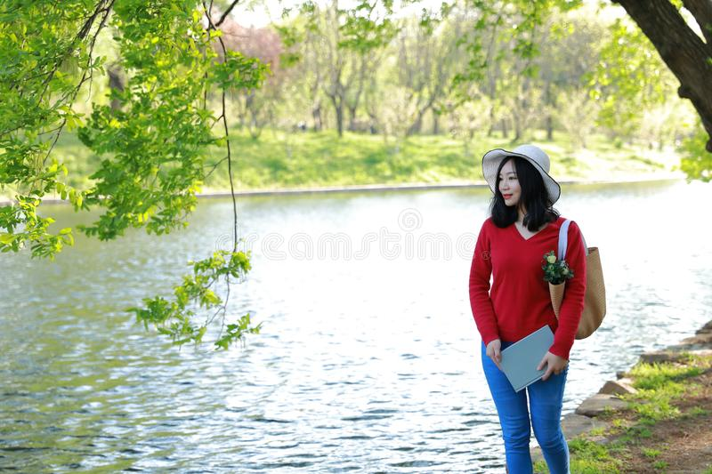Happy Asian Chinese woman beauty girl smile read a book walk by lake in forest spring park sit on bench enjoy cozy life stock photo