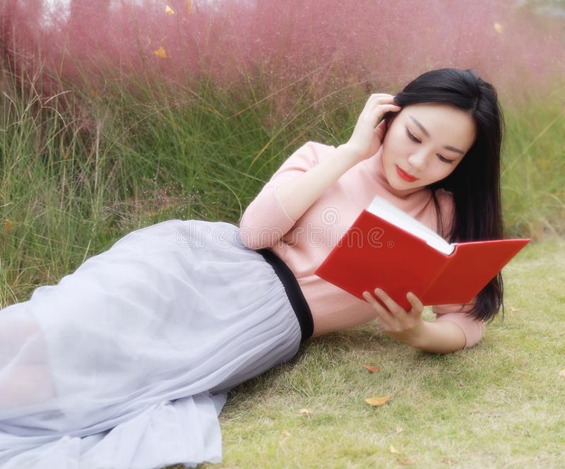 Happy Asian Chinese woman girl lying on grass dream pray flower field autumn fall park lawn hope nature read book knowledge. Pink colour grass lawn, rose hermosa stock photo