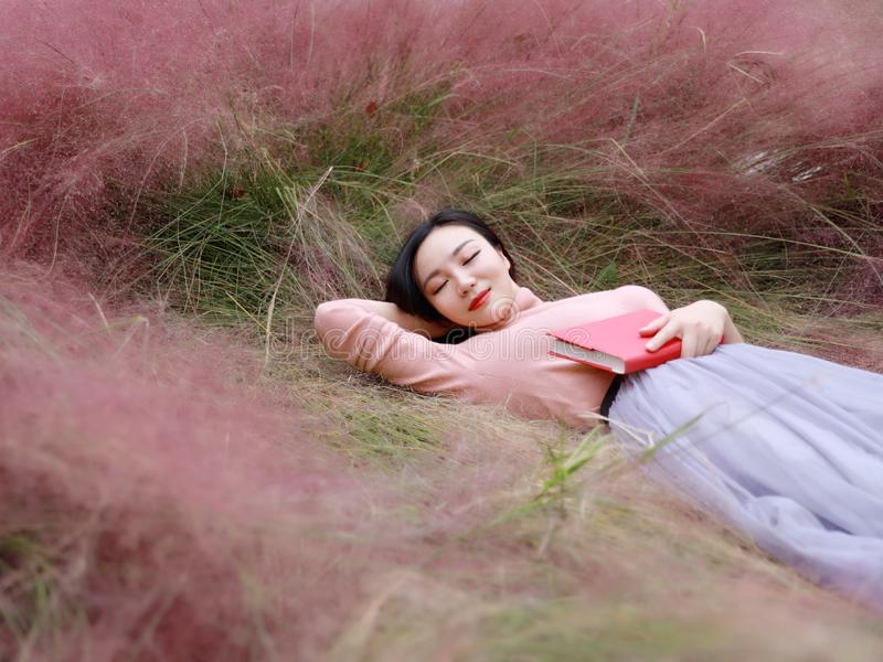 Happy Asian Chinese woman girl lying on grass dream pray flower field autumn fall park lawn hope nature read book knowledge stock images