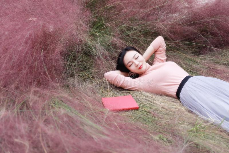Happy Asian Chinese woman girl lying on grass dream pray flower field autumn fall park lawn hope nature read book knowledge. Pink colour grass lawn, rose hermosa stock photography