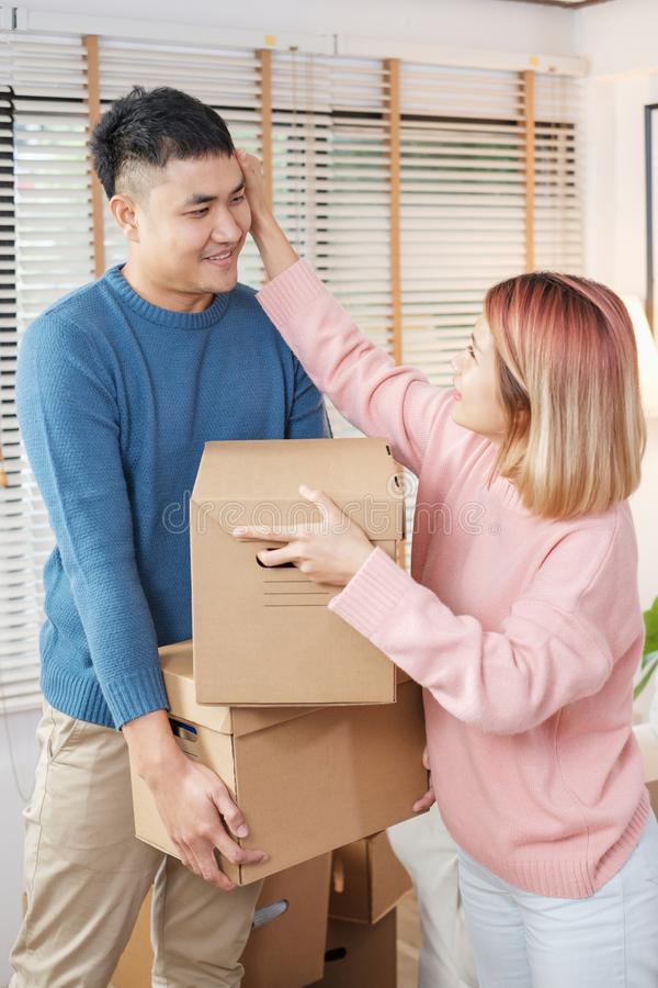 Happy asian couple carry cardboard boxes while moving to new house in living room.unpacking for new home.woman wipe the sweat her royalty free stock image