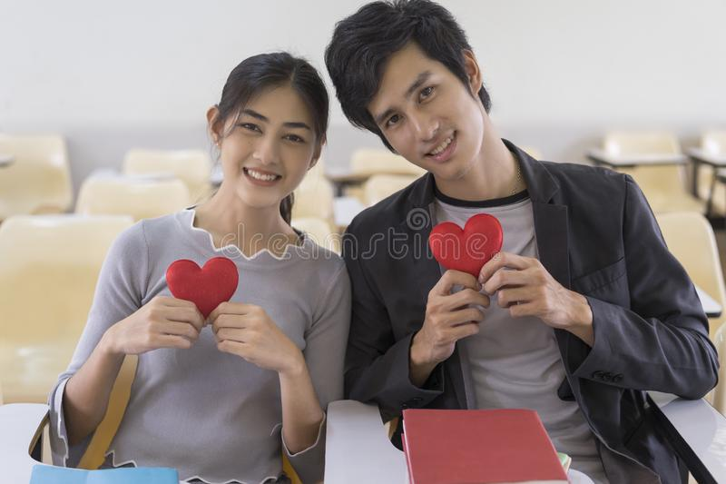 Happy asian couple in love sitting in classroom, holding red heart shape, love symbol royalty free stock images