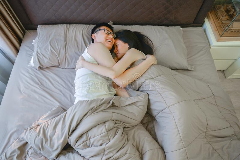 Happy Asian couple in love, sleeping together on bed royalty free stock photos