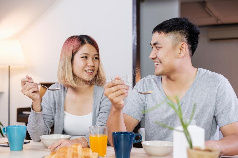 happy asian couple in pajamas sitting at table in kitchen at home in morning and having cereal breakfast together. royalty free stock image
