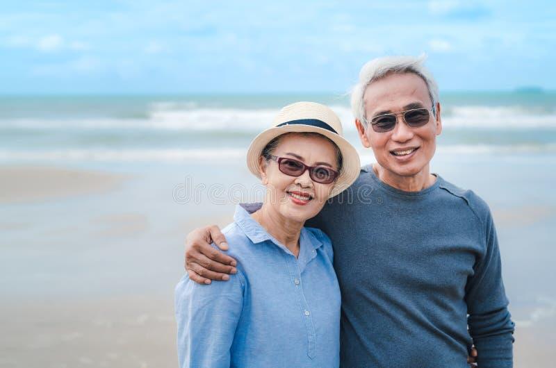 Happy asian couple senior eldery retirement resting at beach honeymoon stock images