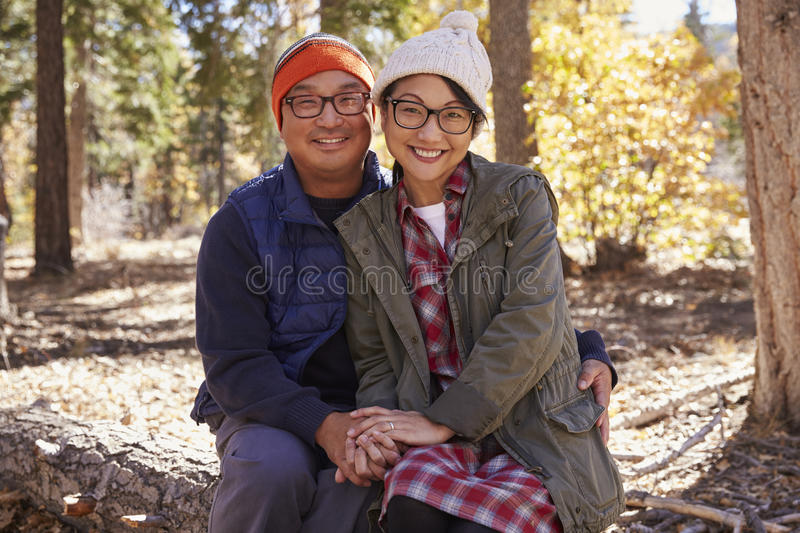 Happy Asian couple sitting in a forest looking to camera stock photo