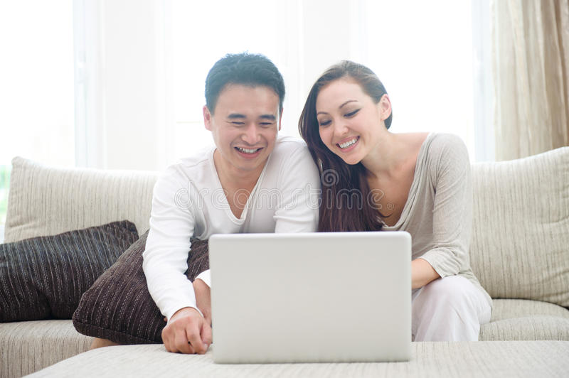 Happy Asian Couple Using Laptop stock photography