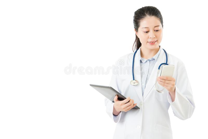 Happy asian doctor holding digital tablet using smartphone. Isolated on white background. health and medical concept royalty free stock images