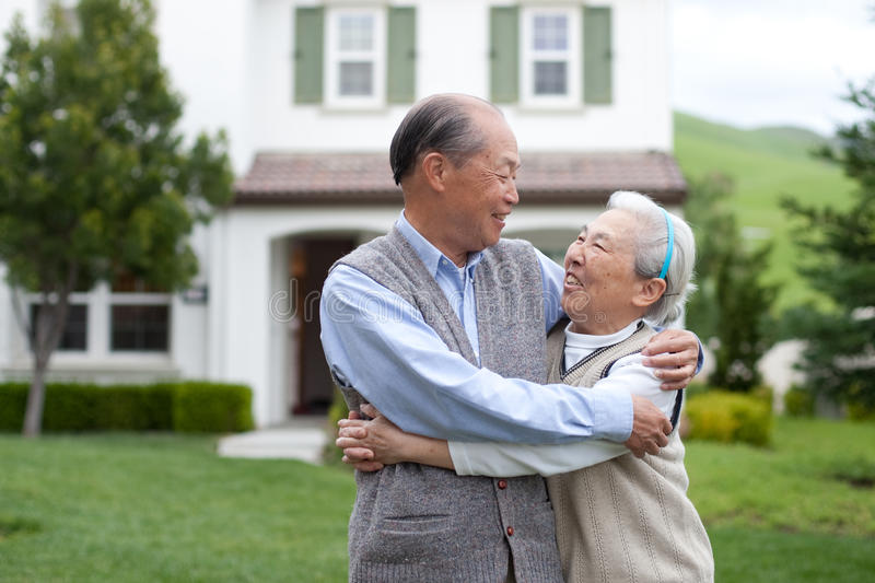 Happy Asian Elderly Couple In Front Yard Stock Images