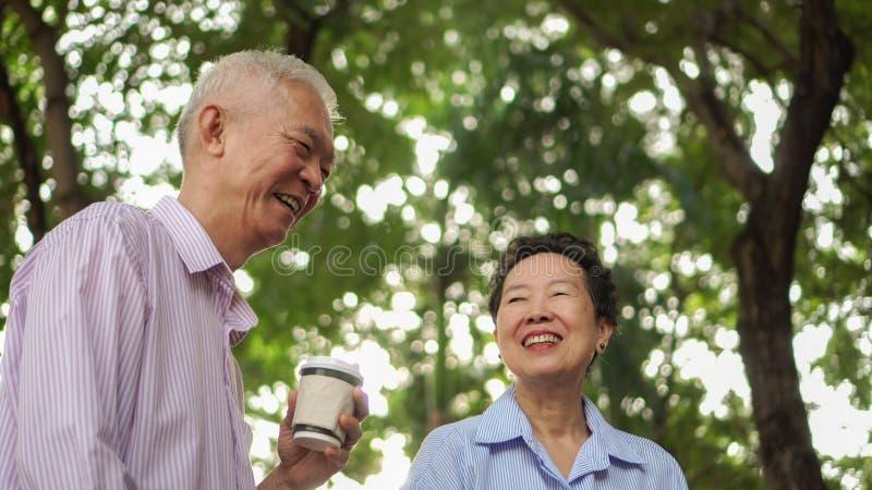 Happy Asian elderly couple morning walk in green city while drin. Happy Asian elderly couple morning walk in green city drinking coffee and talking stock photos