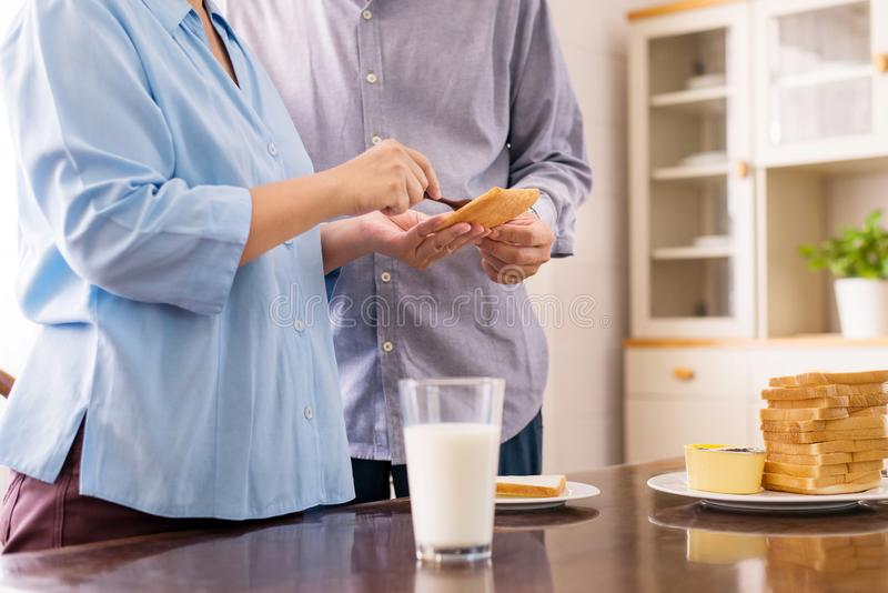 Happy asian elderly couple preparing healthy food for breakfast with bread and butter,Retirement senior lifestyle living concept,C stock photo