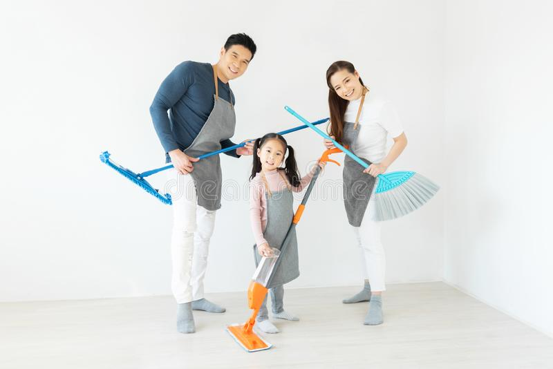 Happy Asian Family dancing and holding cleaning equipment. Having Fun. Happy Asian Family dancing and holding cleaning equipment like playing guitars in a white stock image