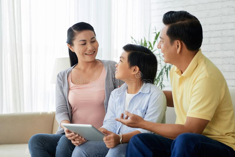 Family spending time together. Happy Asian family with digital tablet having fun in living room stock photo