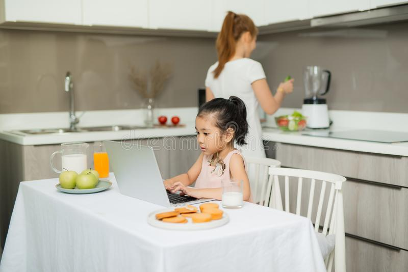 Happy Asian family are eating breakfast and see digital tablet in the kitchen at home. Healthy food and Morning activities.  royalty free stock photography