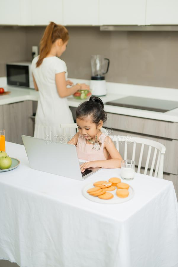 Happy Asian family are eating breakfast and see digital tablet in the kitchen at home. Healthy food and Morning activities.  stock photos