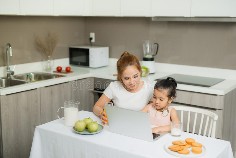 Happy Asian family are eating breakfast and see digital tablet in the kitchen at home. Healthy food and Morning activities.  stock images