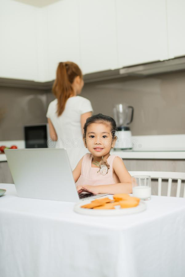 Happy Asian family are eating breakfast and see digital tablet in the kitchen at home. Healthy food and Morning activities royalty free stock images