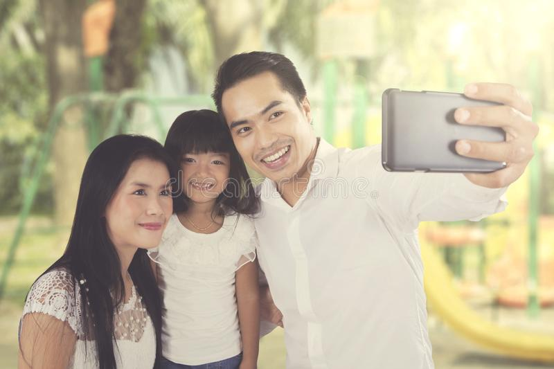 Asian family taking selfie at the park royalty free stock images