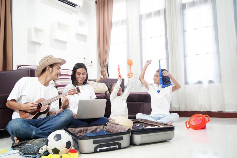 Happy asian family on a floor at home planning vacation travel trip stock images